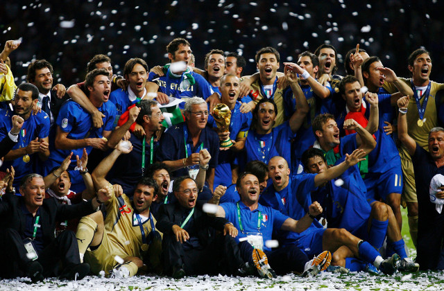 BERLIN - JULY 09:  The Italian players and coaching staff celebrate with the World Cup trophy following their victory in a penalty shootout at the end of the FIFA World Cup Germany 2006 Final match between Italy and France at the Olympic Stadium on July 9, 2006 in Berlin, Germany.  (Photo by Shaun Botterill/Getty Images)